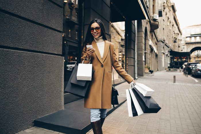 Shopping. Black Friday. Technology. Woman with shopping bags is using a smartphone and smiling while walking down the street
