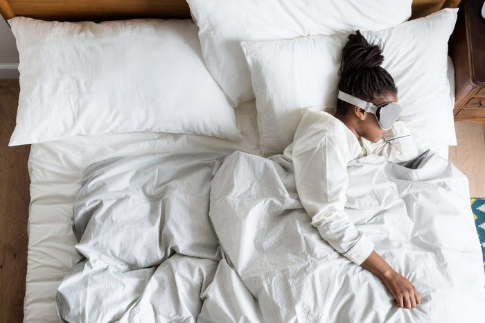 African American woman on bed sleeping with an eye cover