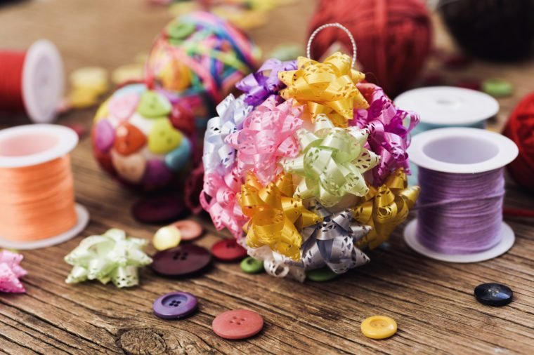 closeup of some handmade christmas balls, mad with ribbon bow, strings and buttons of different colors, and a pile of different haberdashery items on a rustic wooden surface