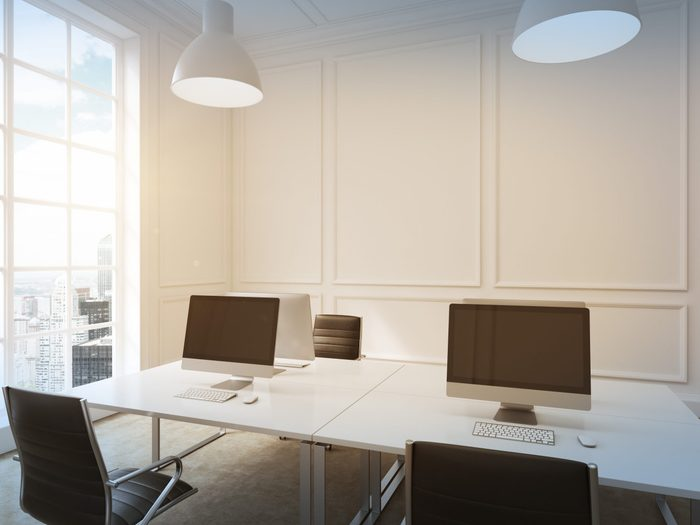 Four workplaces arranged in pairs symmetrically with computers only on them. Four leather chairs around the table. Window with city view to the left. Filter. 3D rendering.