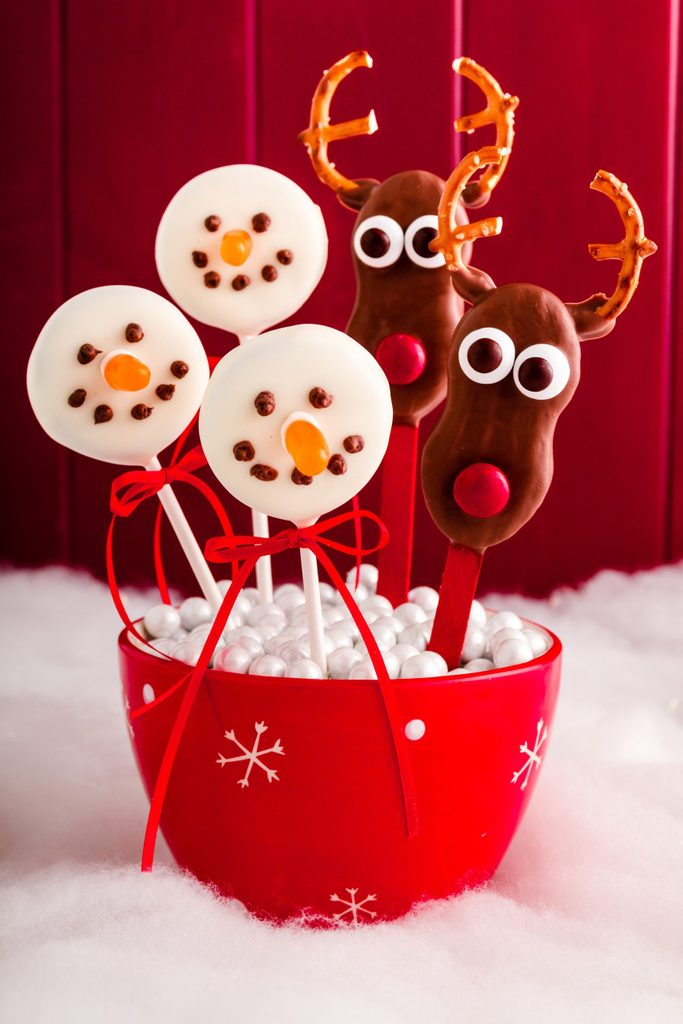 Homemade snowmen and reindeer cake pops on stick in red snowflake bowl