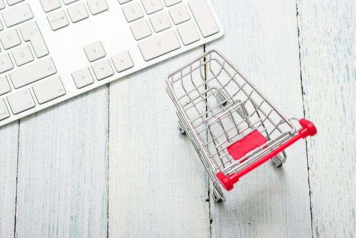 shopping cart and keypad on white wood table, web shopping background