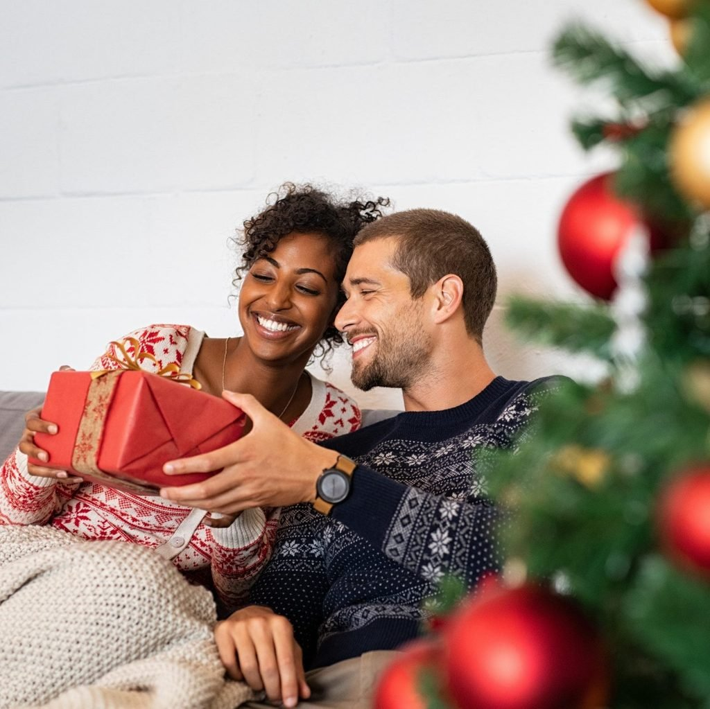 Romantic multiethnic couple exchanging gifts near decorated christmas tree. Smiling man in sweater giving christmas present surprise to african woman while relaxing on couch. Boyfriend and girlfriend.