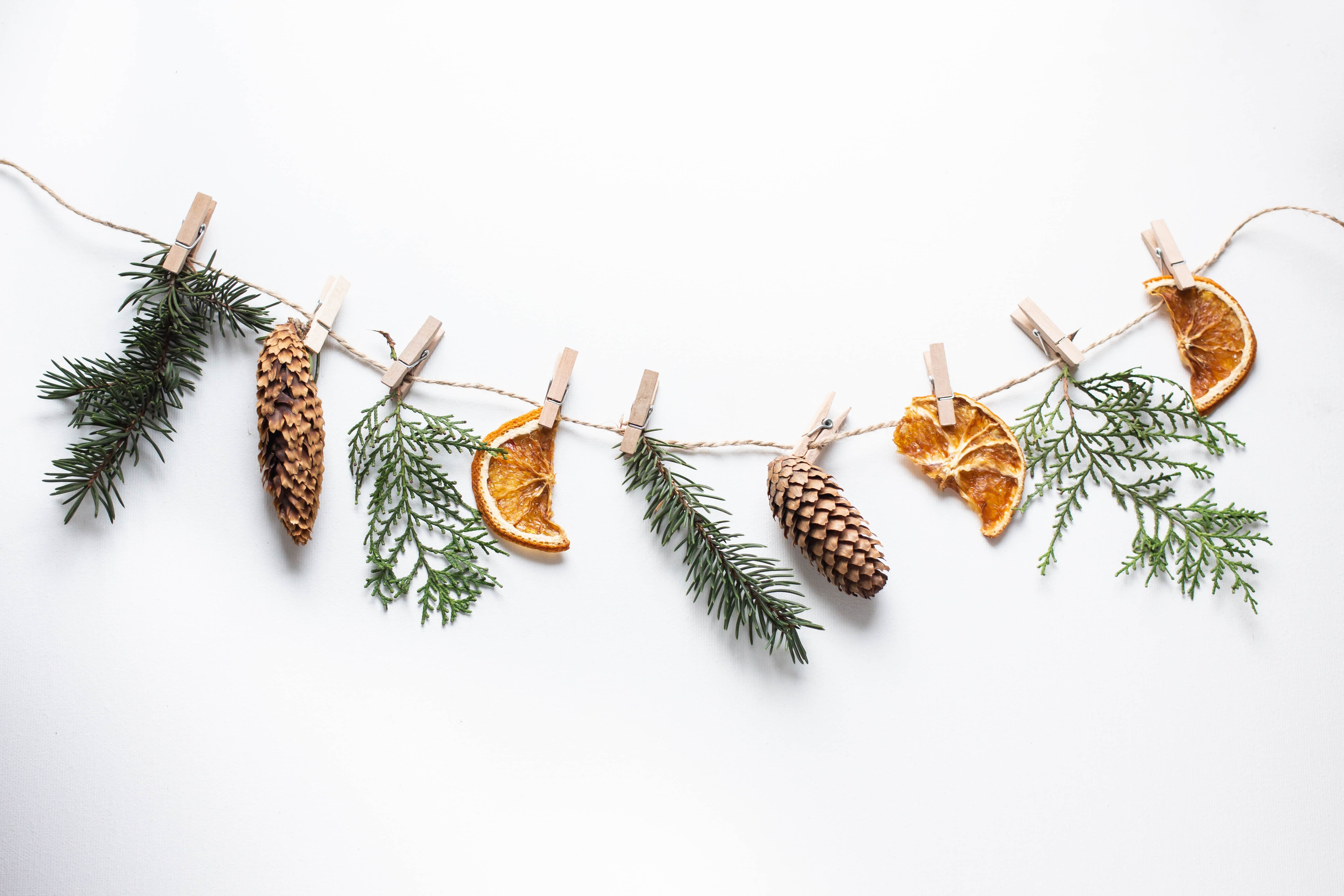 Christmas composition. Christmas garland made of tree branches, cones, dried orange slices and thuja branches on white background. Flat lay, top view, copy space.