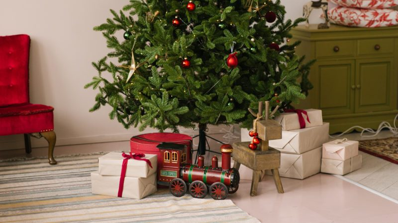 Christmas gift boxes, toy steam engine under the Christmas tree with lights in the living room