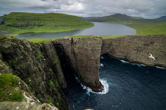 Traelanipa cliff is seen rising over the ocean next to lake Sorvagsvatn in the Faroe Islands