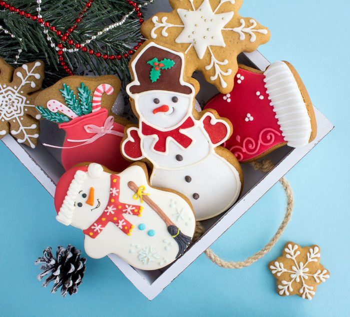 Christmas cookies in the white wooden tray on on the blue background. Top view. Copy space.
