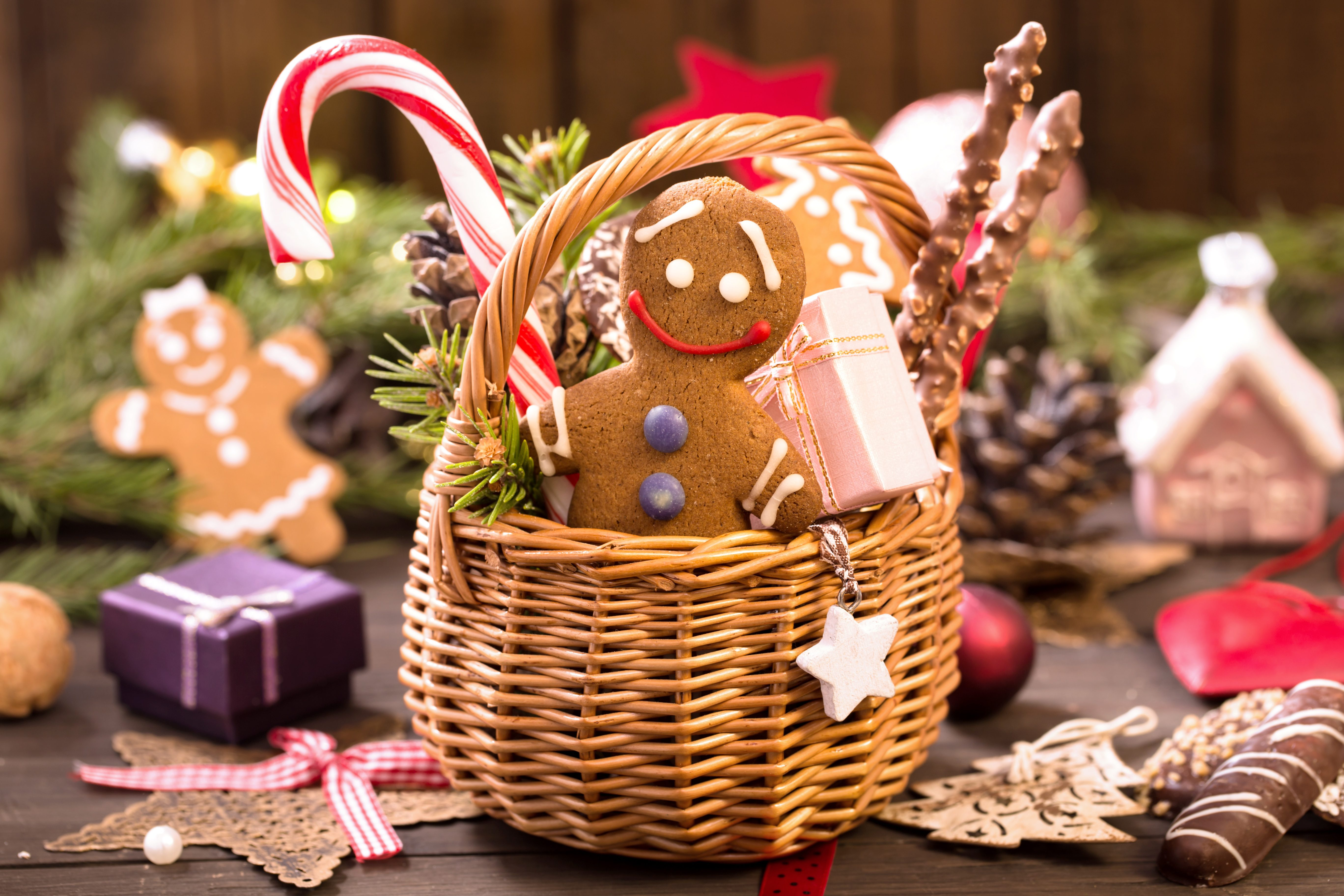 Basket of various Christmas treats, gingerbread man, gifts and decorations on the table