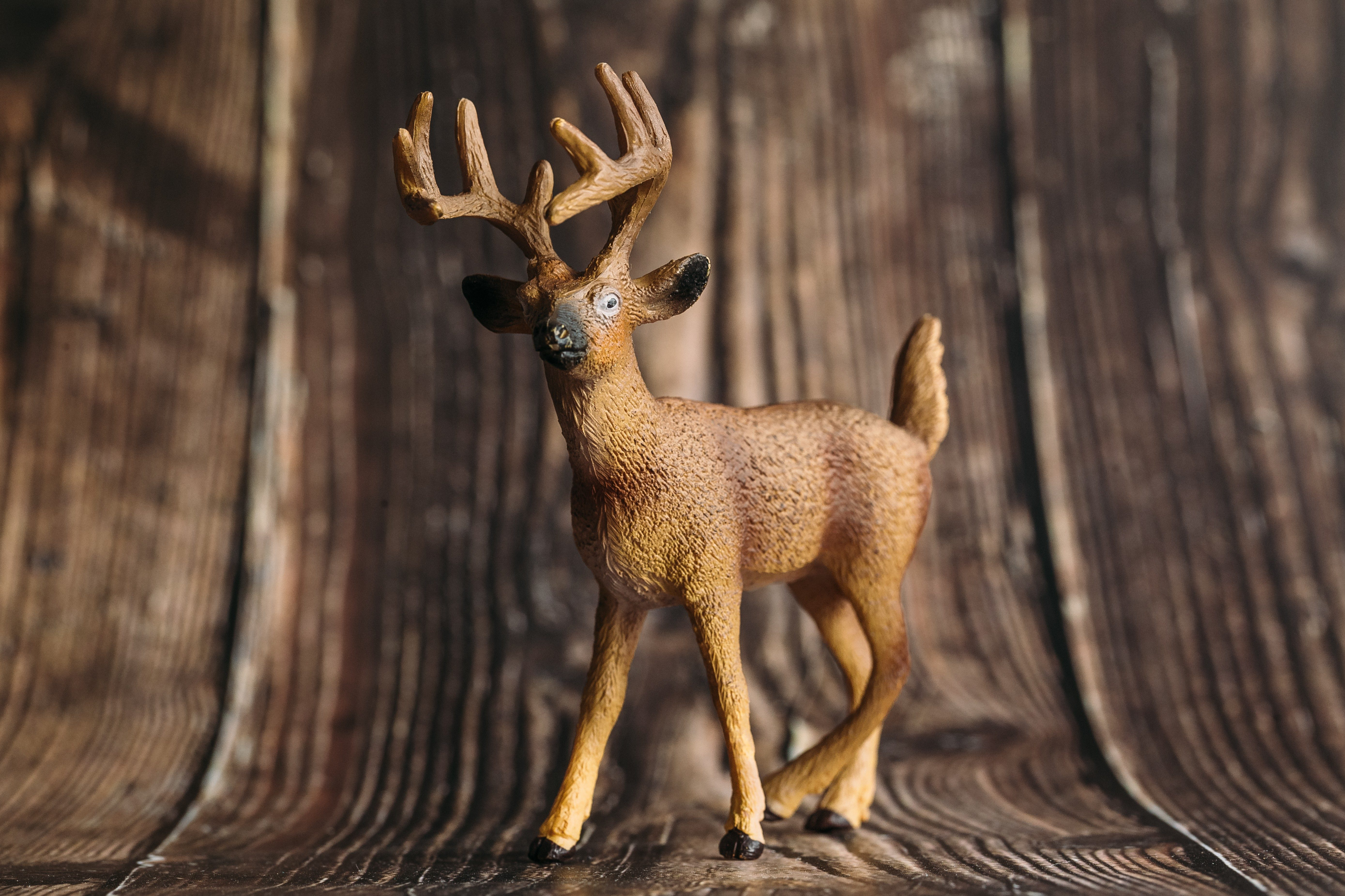 figure of a toy deer on a wooden background