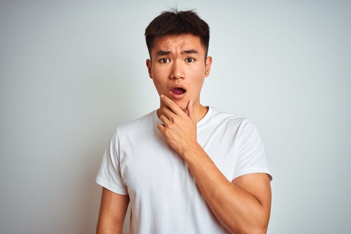 Young asian chinese man wearing t-shirt standing over isolated white background Looking fascinated with disbelief, surprise and amazed expression with hands on chin