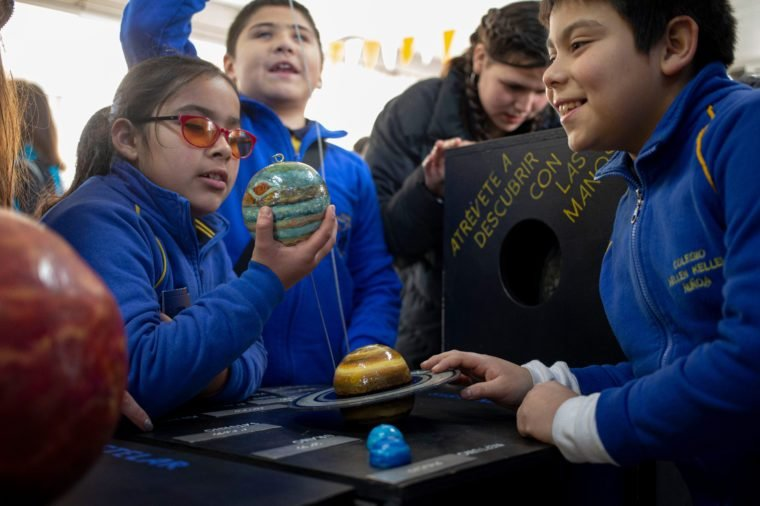 Blind school children take part in a sensorial experience with tools created by NASA and Edinburgh University to experience an eclipse, during an event in the Helen Keller school in Santiago, Chile. 25 June 2019