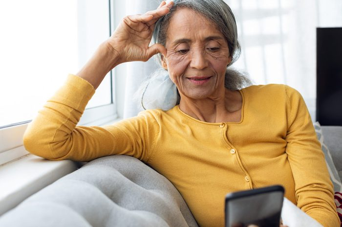 Front view of African American Woman using smartphone. Authentic Senior Retired Life Concept