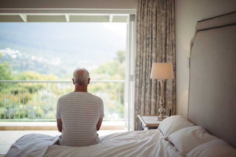 Senior man in bedroom looking at the view through the window