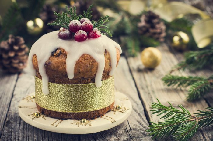 Christmas fruitcake decorated with icing and berries, toned