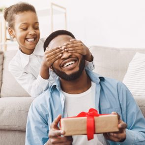Father's day. Happy daughter congratulating dad and giving present at home