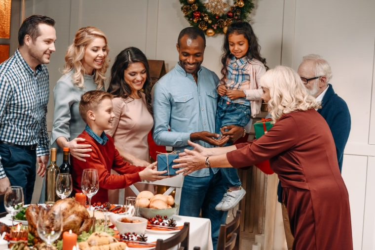 happy senior grandparents presenting gifts to large family