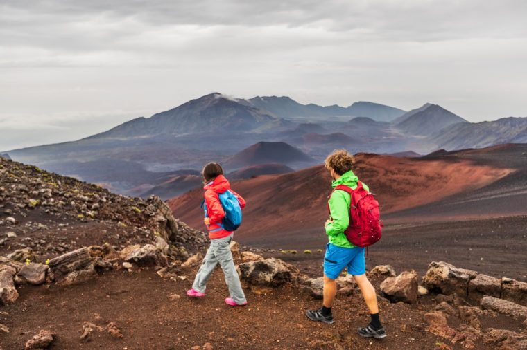 Hawaii volcano hikers people walking hiking on mountains in Haleakala volcanic background landscape. Two young tourists couple on trek hike outdoors.