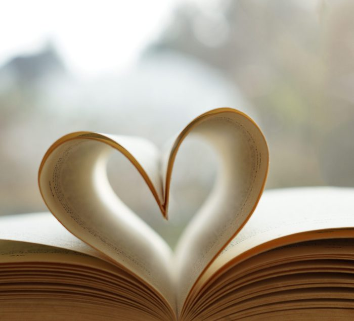 Heart from page of book for valentine's day concept with blurred bright light background and vintage tone.