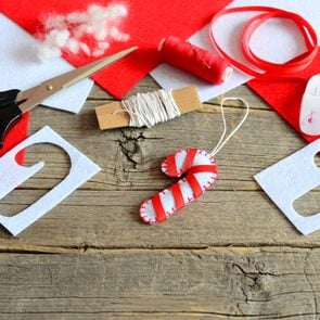 Felt Christmas candy cane ornament, scissors, paper template, thread, needle, red and white felt pieces and scraps, filler, ribbon on old wooden background. Christmas DIY concept. Kids holiday crafts