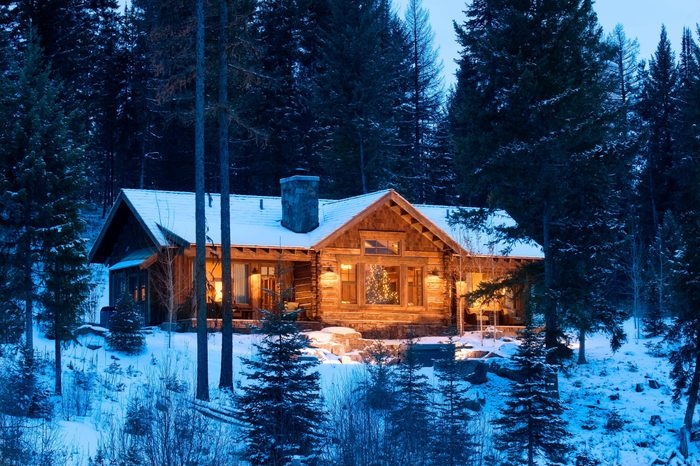 exterior of a cabin with a christmas tree in the center picture window