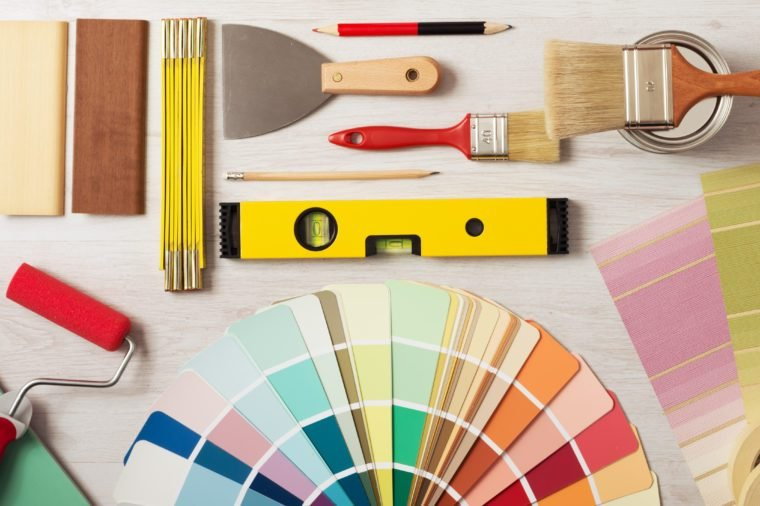 Decorator holding a painting roller and painting a wooden surface, work tools and swatches at bottom, banner with copy space