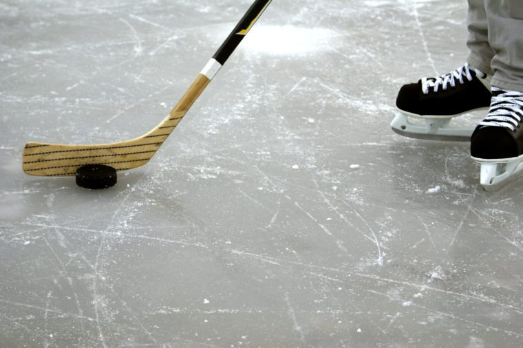 a hockey stick and puck and ice skates on the ice