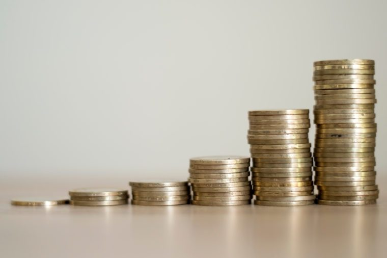 stacks of coins with growth between stacking limits on white background