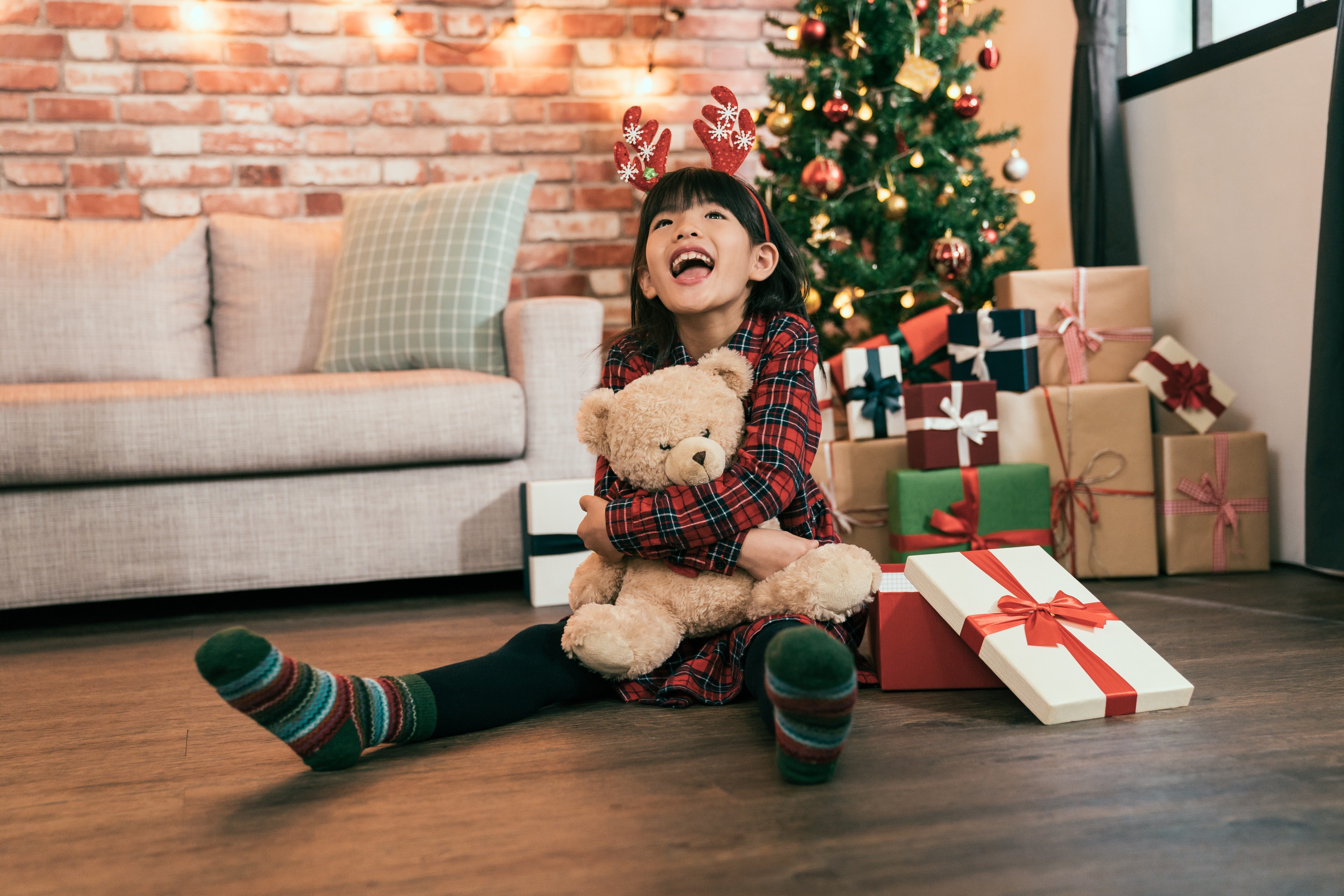 little girl cheerful got christmas present and smiling looking to the roof in the bright living room. merry xmas and happy new year are coming. excited kid holding teddy bear with decorated tree.