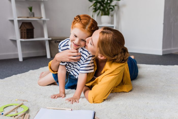 mother kissing her cute little daughter in cheek on floor at home