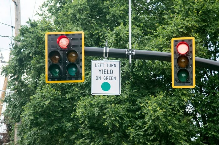 Left Turn Yield On Green Sign attached to a traffic light pole made in white black and green color