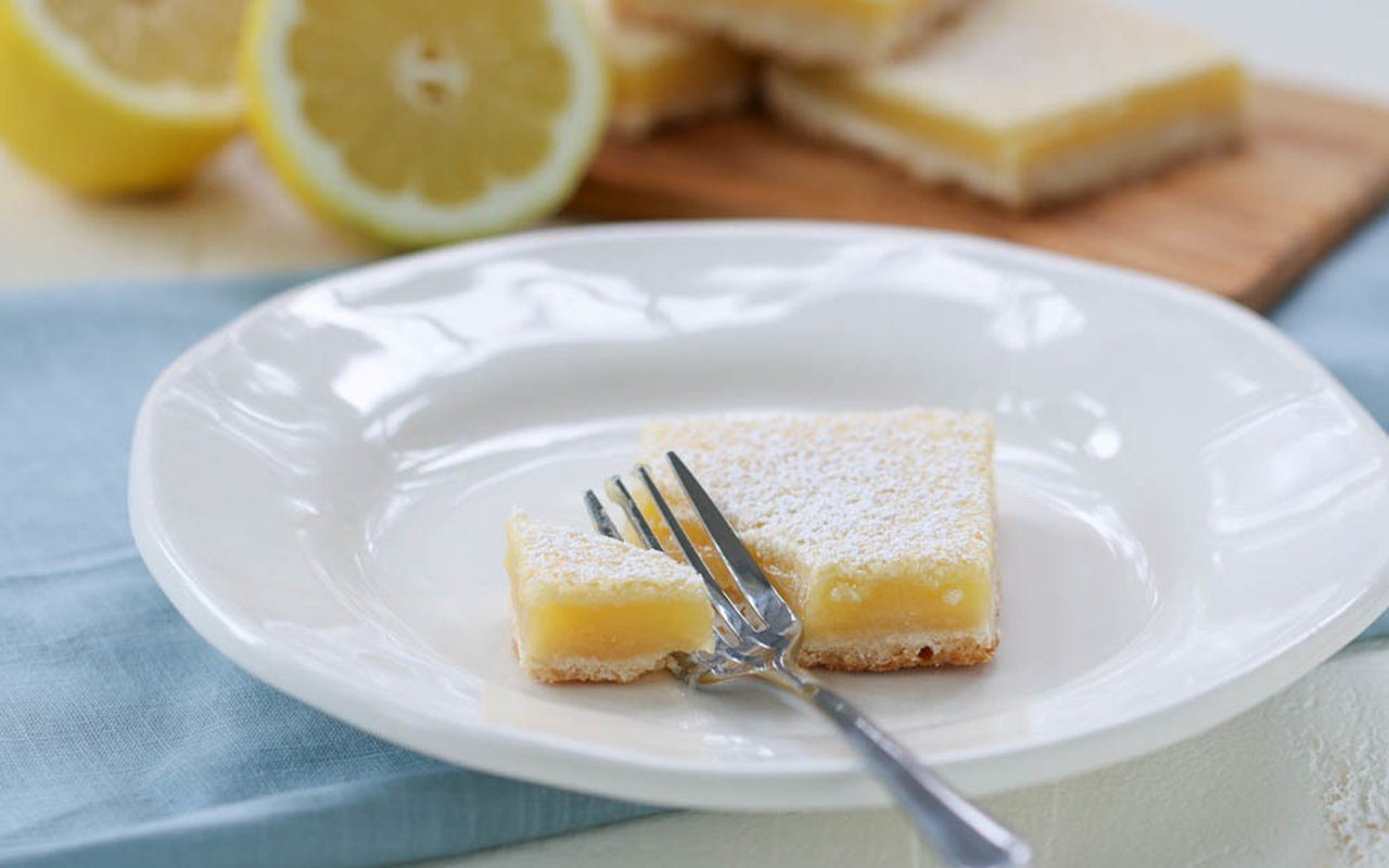 Single lemon bar on a plate with a fork
