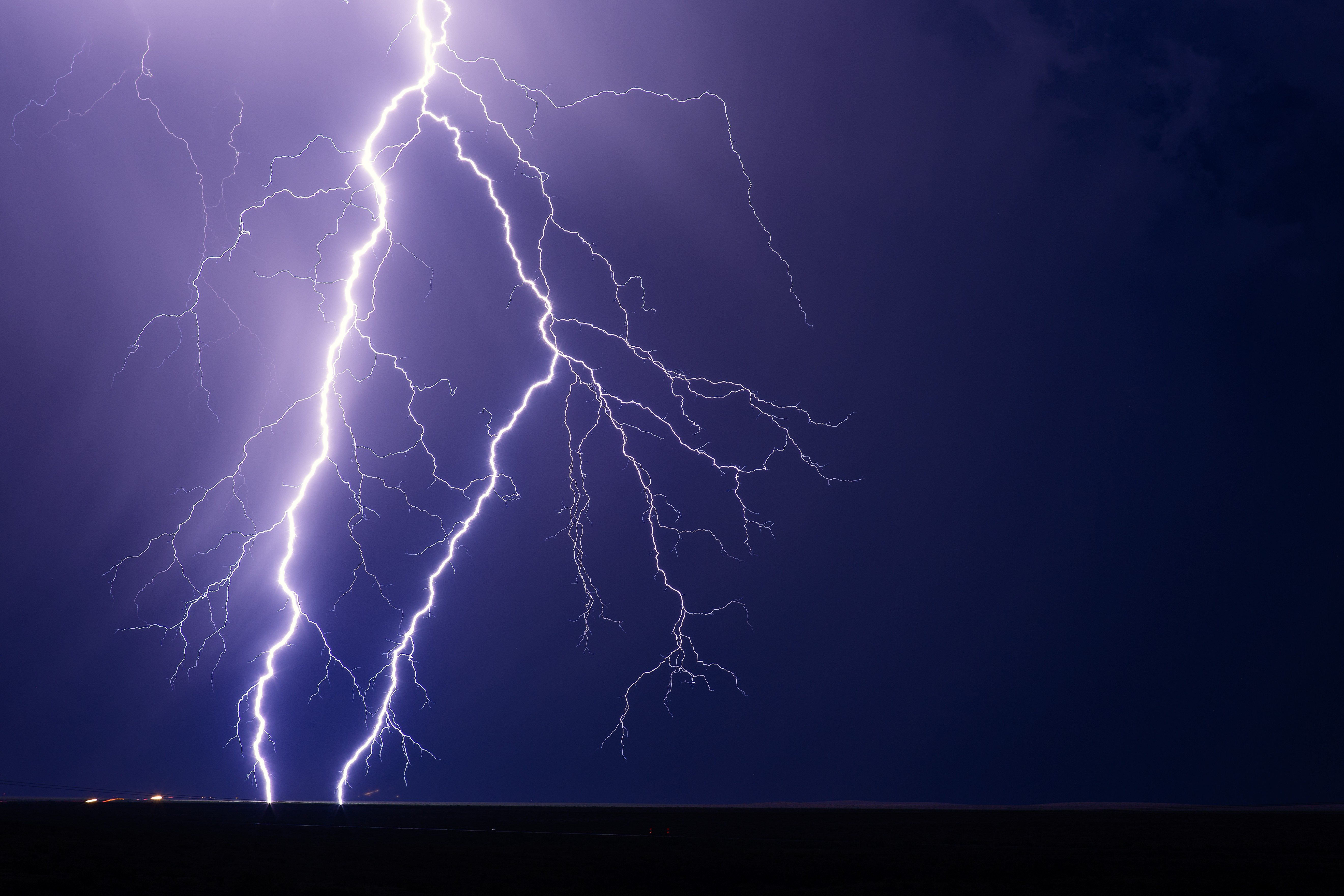 Lightning bolts strike from a storm with a night sky background.