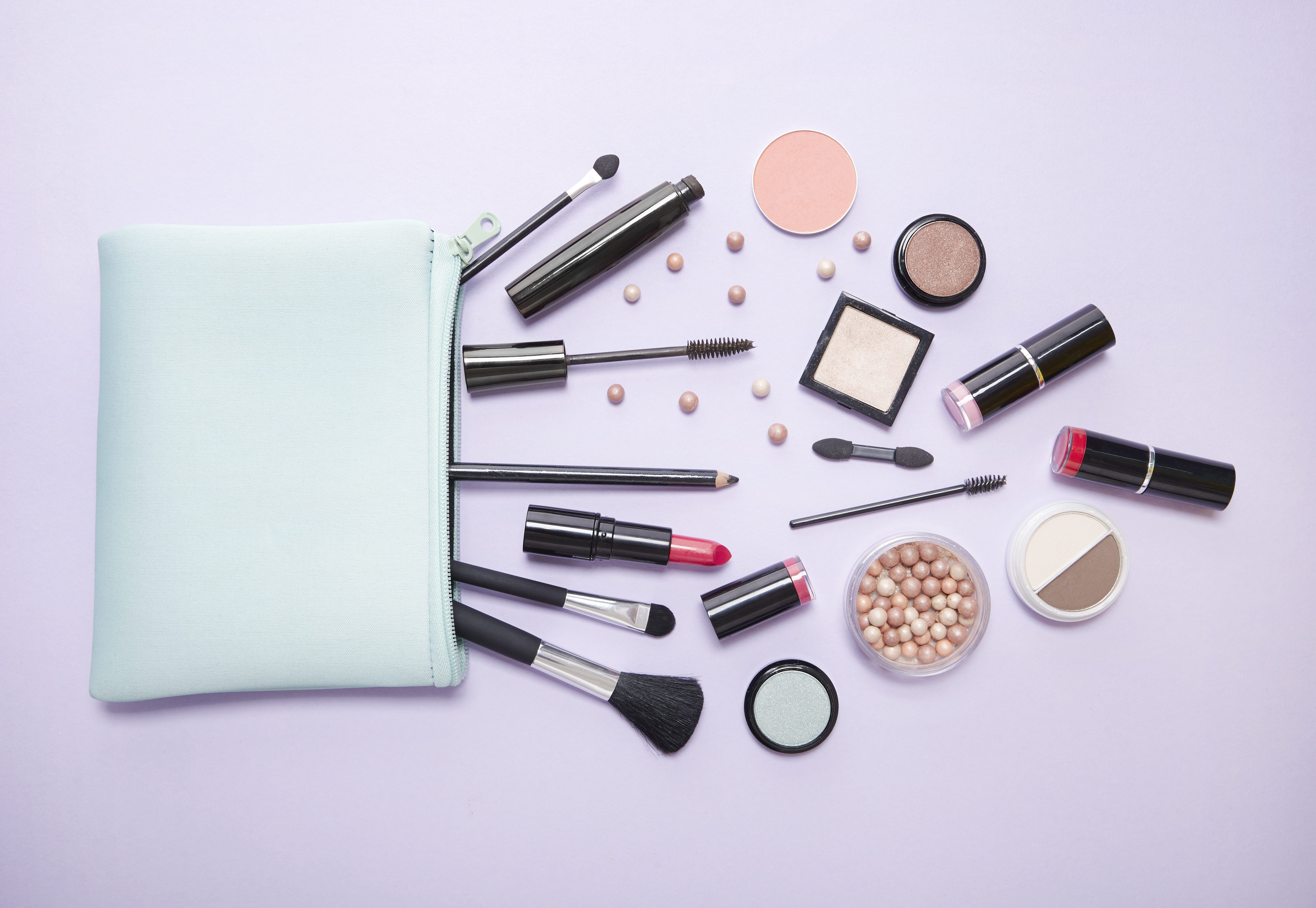 Aerial view of a blue make up bag, with cosmetic beauty products spilling out on to a pastel purple background