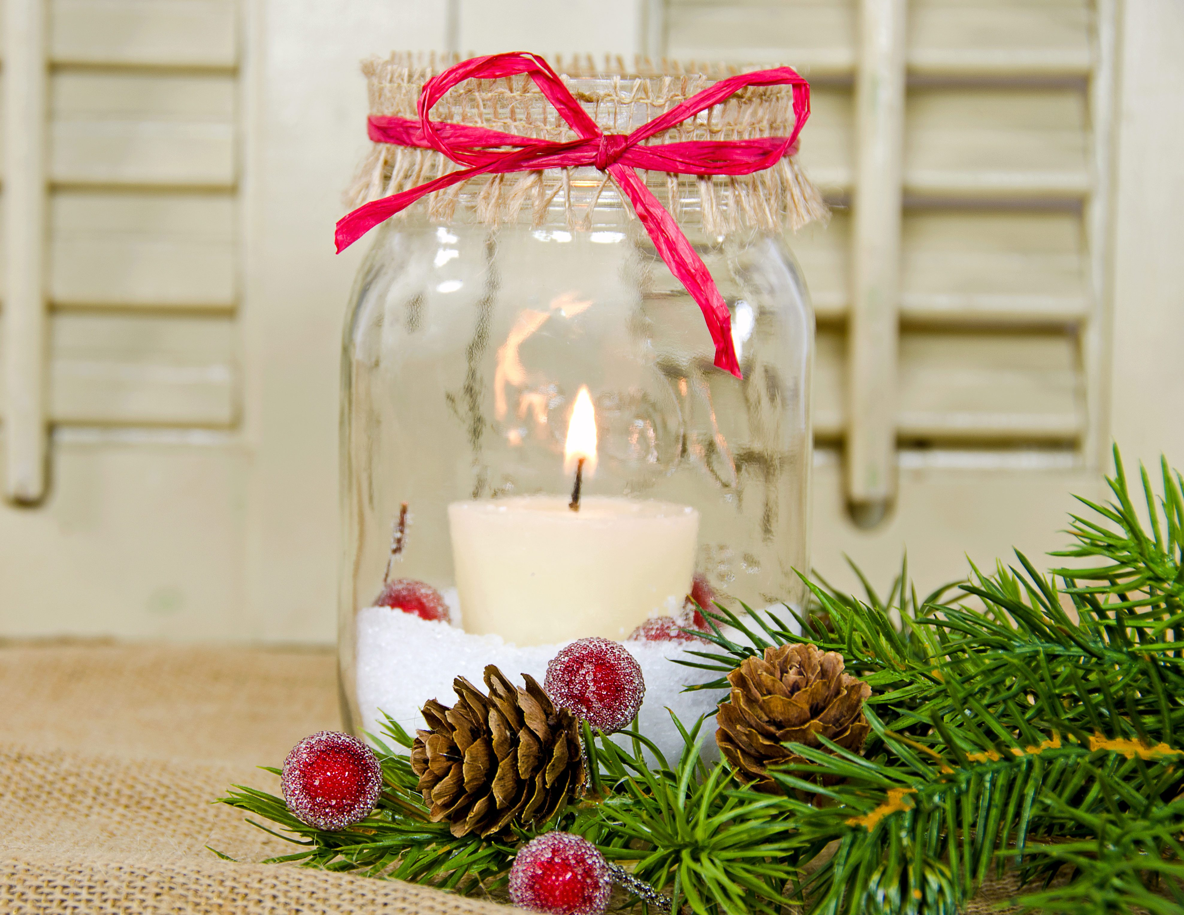 Christmas candle in a mason jar with pine bough and sparkling red berry