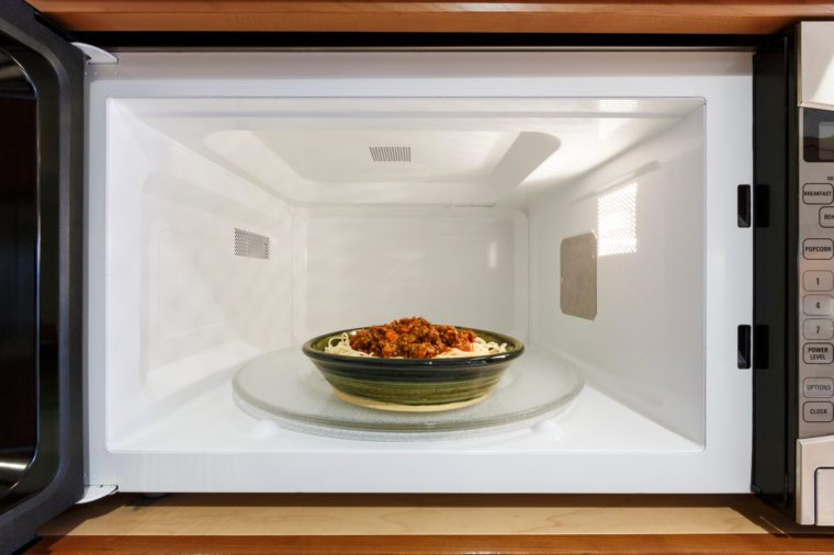 Kitchen home appliances cooking reheating plate bowl dish meal dinner of cooked spaghetti pasta with Bolognese tomato meat sauce in microwave oven