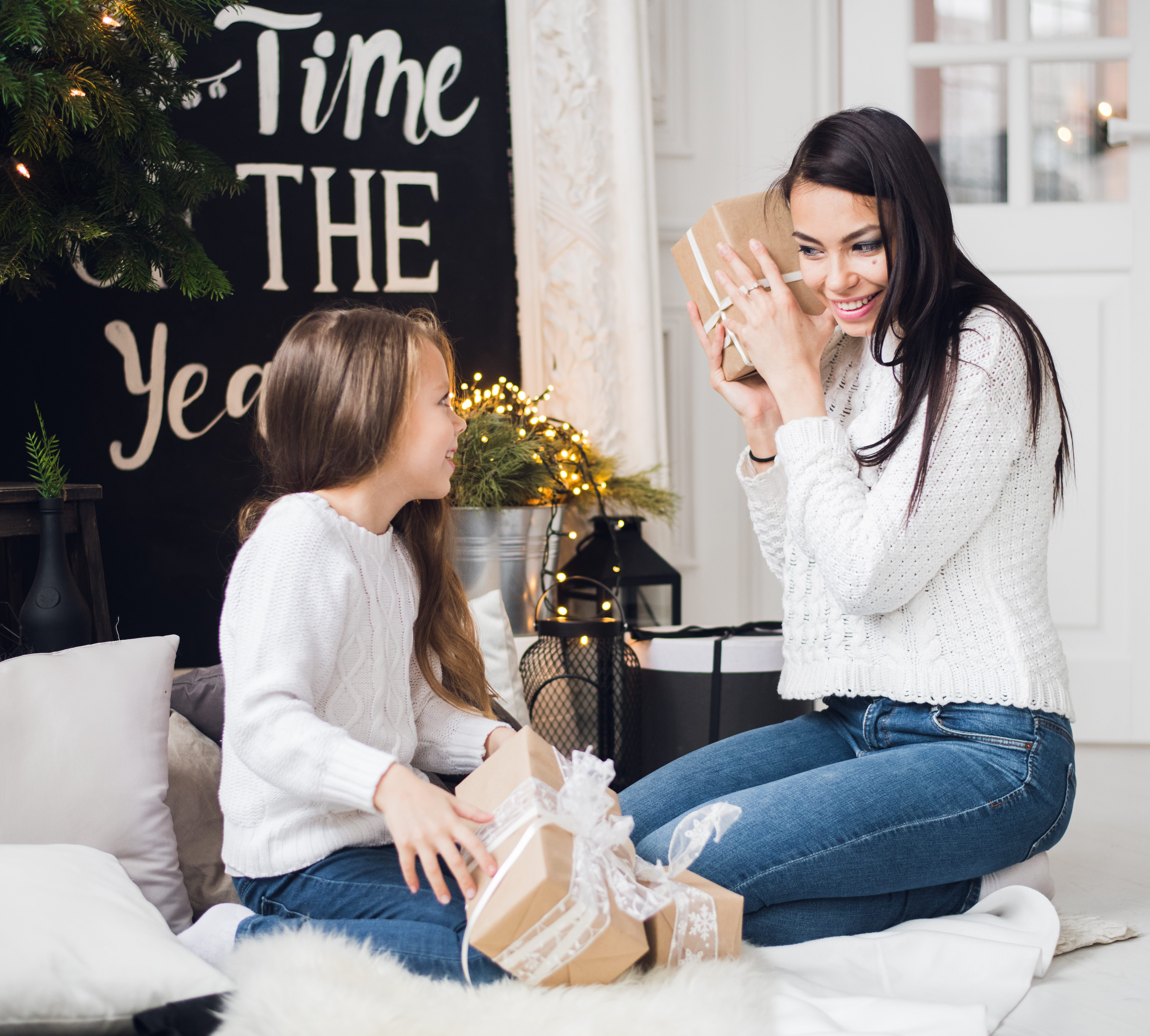 Merry Christmas and Happy Holidays. Cheerful mom and her cute daughter girl opening a Christmas present. Parent and little child having fun near Christmas tree indoors
