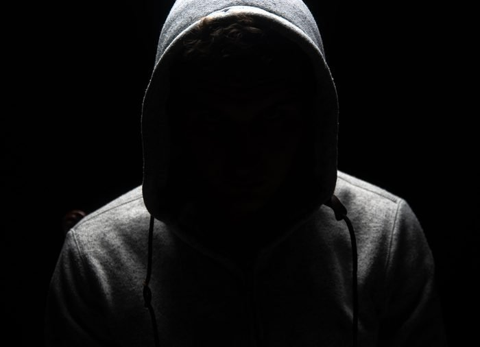 A man who's wearing a hoodie and who's face is concealed by darkness.
