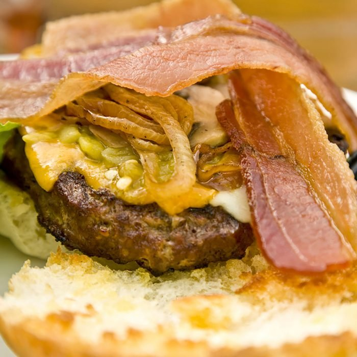 A bacon cheeseburger served open-faced with onions, green chiles and a side of guacamole