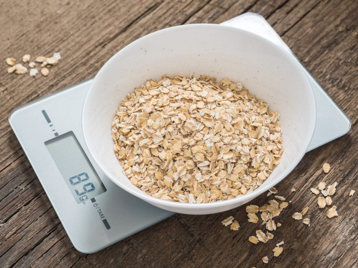 Product weighing concept. Oatmeal in a white bowl on the kitchen scales on wooden background