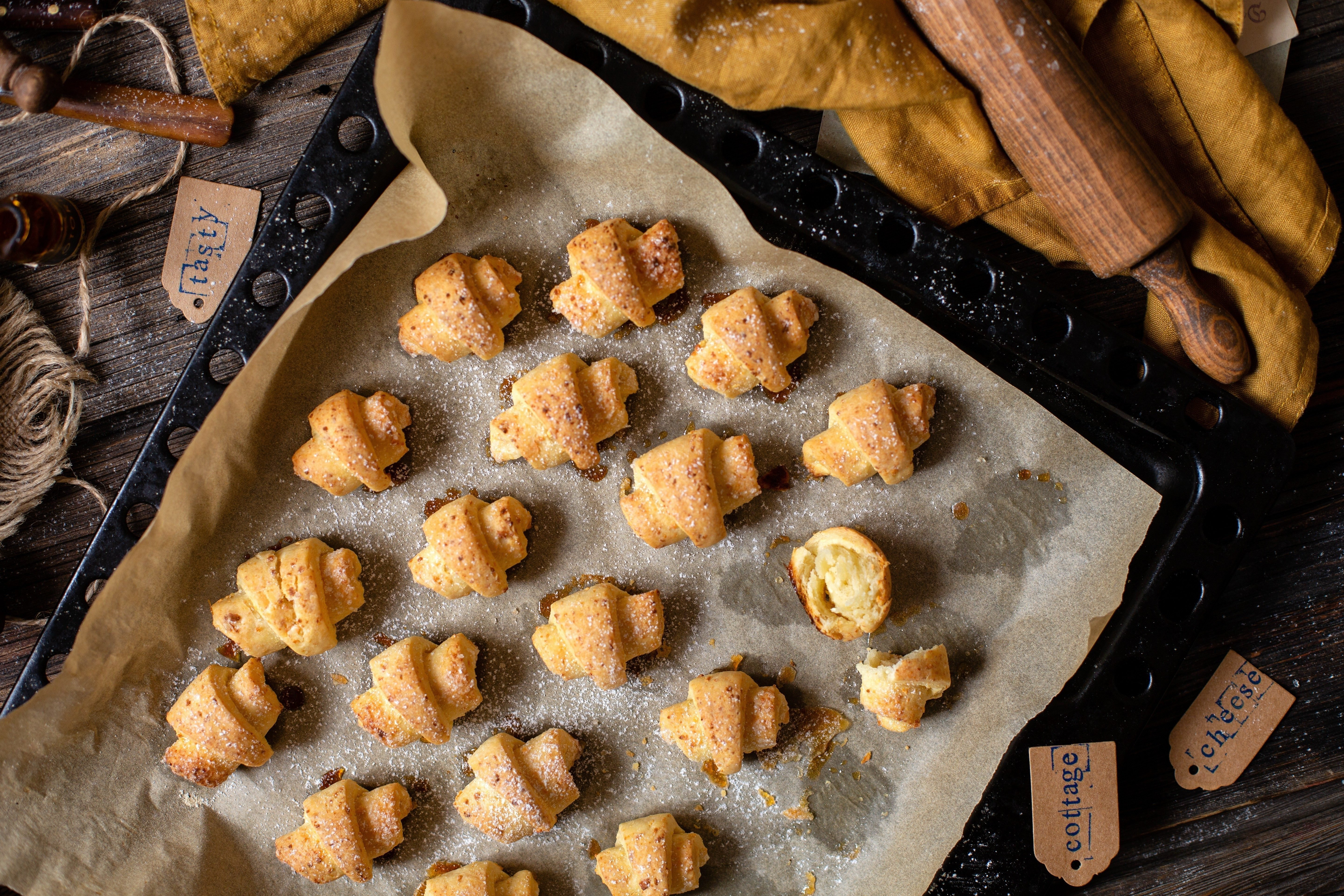 overhead shot of tasty baked rolled or bagels cookies on baking tray with parchment on rustic wooden table with rolling pin and orange napkin