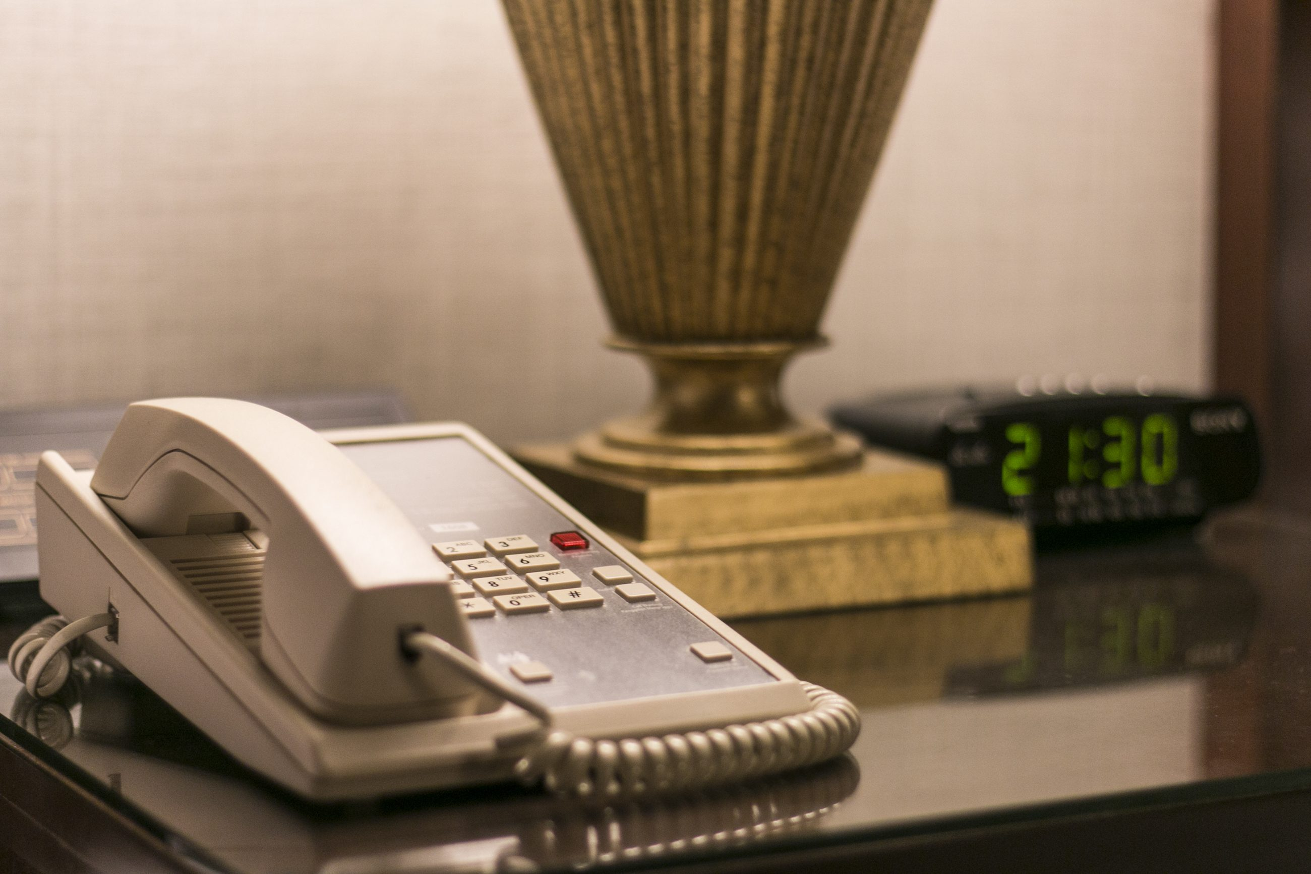 Telephone at hotel room sitting on bedside table along with the table lamp and alarm clock.