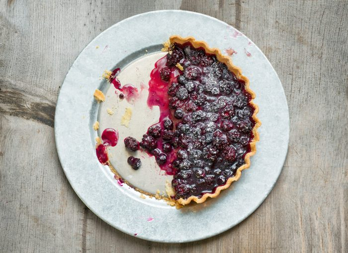 Overhead shot of a blueberry and blackberry tart, half eaten on a galvanized plate and wooden background.