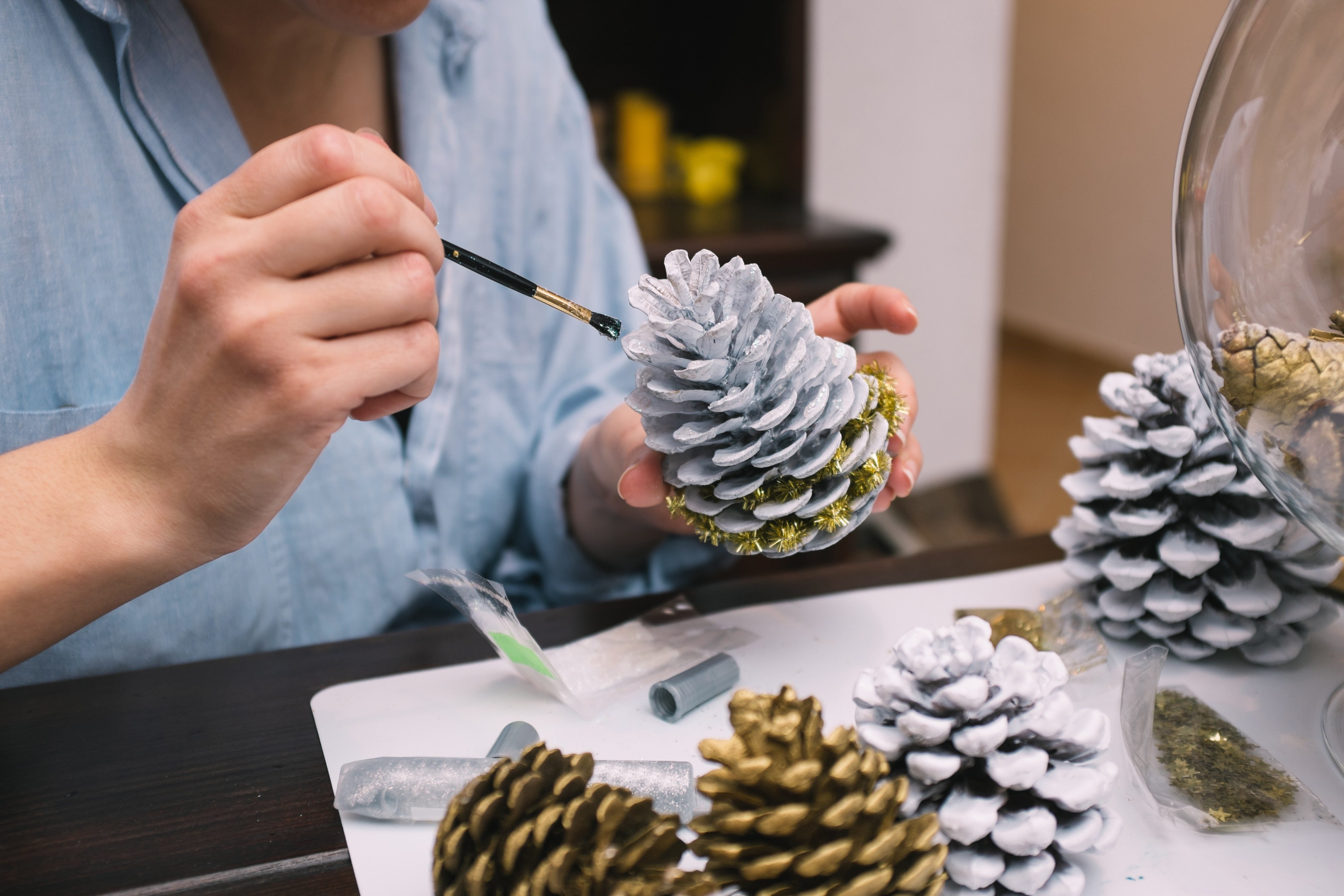 Woman painting pine cones for Christmas