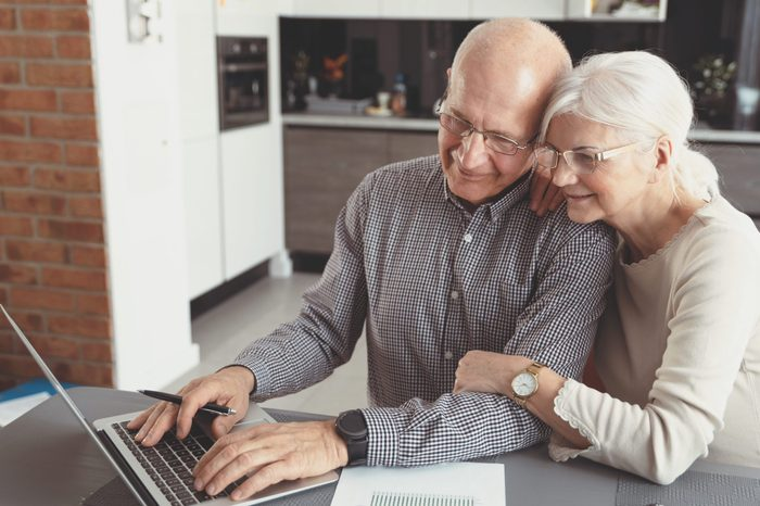 Senior couple paying bills together on laptop. Couple doing some paperwork and calculations at home