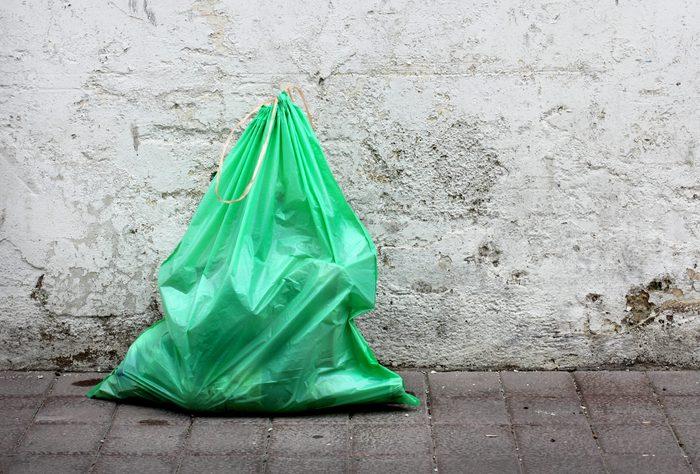Green garbage bag on street