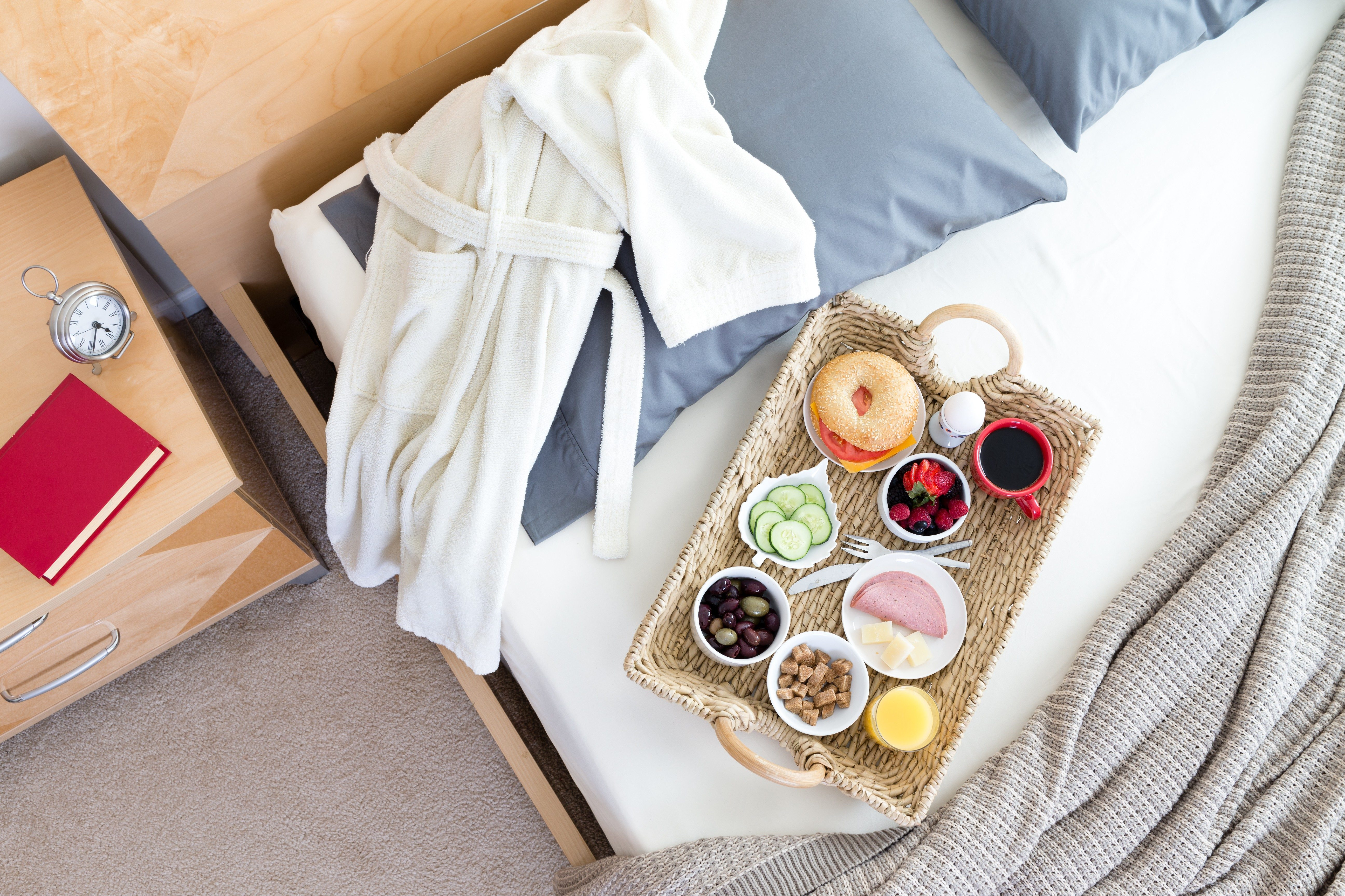 High Angle View of Bathrobe and Breakfast Tray on Unmade Bed Beside Night Table with Red Book in Hotel Room