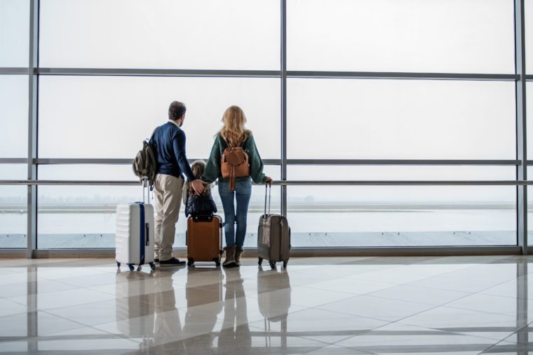 Father, mother and daughter getting ready for the flight. They are standing at departure lounge with suitcases and waiting for the aircraft arrival. Copy space in right side
