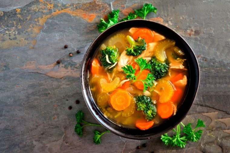 Homemade chicken vegetable soup, overhead view on a dark slate background