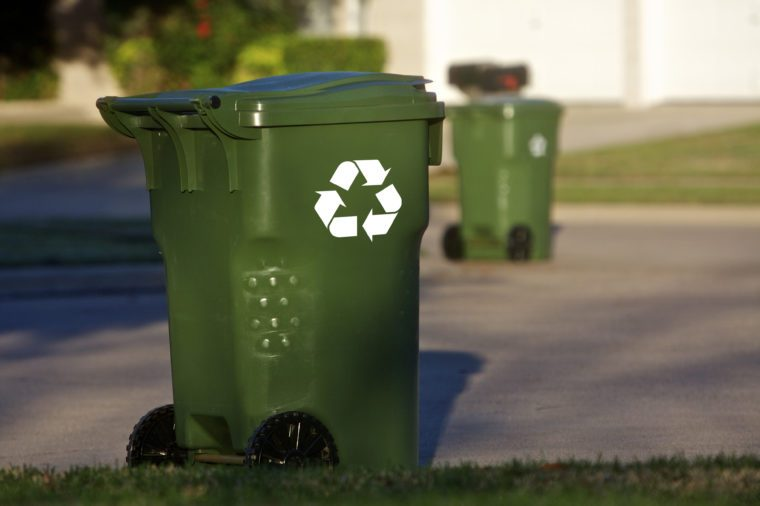 Green recycle bins align a neighborhood street