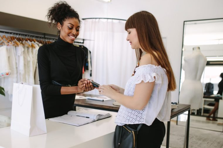 Customer shopping designer wear at a fashion boutique. Customer making payment using a credit card on a point of sale machine.